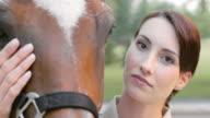 SLO MO Portrait of a bay horse alongside brunette woman video