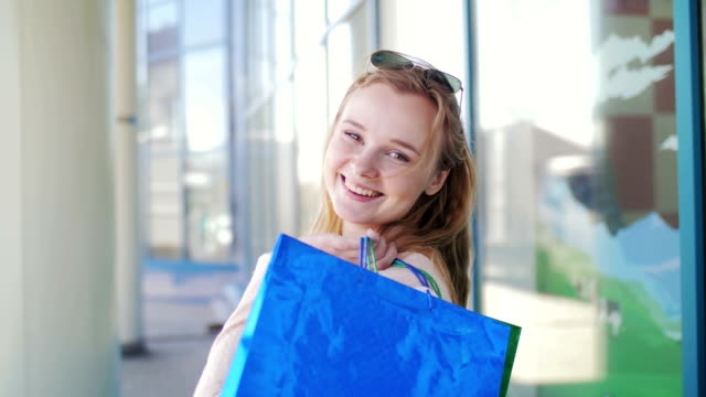 Portrait of a beautiful girl who left the store with shopping. video
