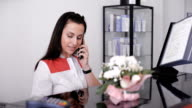 Portrait of a beautiful smiling nurse at desk station while talking on the phone video