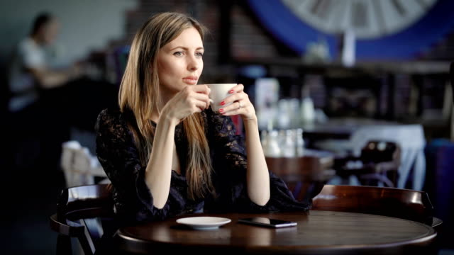 Portrait of a beautiful woman in a cafe or restaurant. A girl drinks tea or coffee and dreams about something video