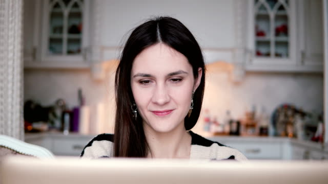 portrait of a beautiful young brunette woman uses laptop in a bright dining video