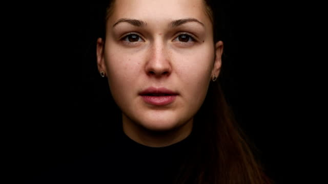 portrait of a beautiful young girl on a black background. close-up. Dolly video