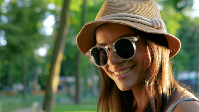 A portrait of a beautiful young woman wearing hat and sun glasses smiling in park video