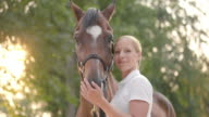 SLO MO Portrait of blonde female with bay horse video