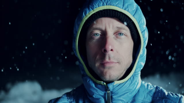 SLO MO Portrait of a blue eyed man in snowfall video