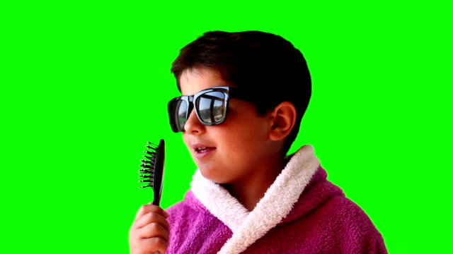 Portrait of a boy in a bathrobe, sunglasses and a comb on green screen video