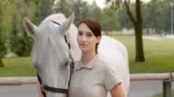 SLO MO Portrait of brunette female stroking white horse video