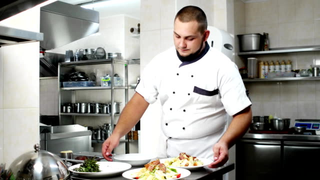 Portrait of a chef, cook checks dishes with salads, ready meals shows, looking at the camera, smiling chef in a chef's form on by professional kitchen video