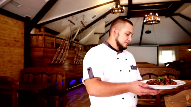 Portrait of a chef in the hall restaurant, the chef are served food guests, taverns, cafes, chef out to visitors, it carries the food on a plate in his hand video