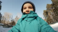 ACTION CAM: Portrait of a cute little boy rides on a sledge in a park in winter video