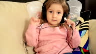 Portrait of a cute little girl listening to music video