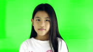 Portrait of a cute little girl smiles looking at camera, Green screen video