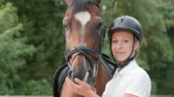 SLO MO Portrait of female rider bonding with bay horse video
