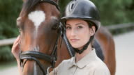 SLO MO Portrait of a female horse rider posing with her bay horse video