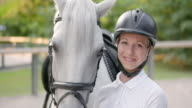 SLO MO Female rider posing with her white horse. video