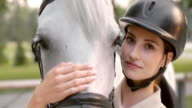 SLO MO Brunette female rider stroking white horse on nose video