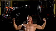 Portrait of a fitness man doing exercises with dumbbells at gym video