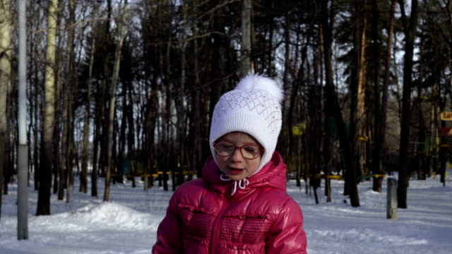 Portrait of a girl child in glasses, a white cap and a red jacket. The girl smiles and shows emotion in front of the camera. Spring Sunny morning in the Park. video