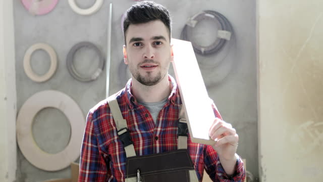 4K Portrait of a happy carpenter holding a wooden board on his shoulder. video
