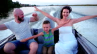 portrait of a happy family on vacation, family in a boat, Mom and Dad spend time with his son having fun laughing walking in nature, parents with a child on a summer outing video