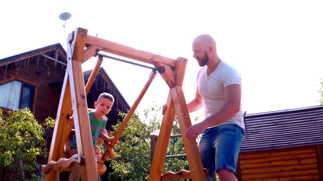 Portrait of a happy father and son, Child riding on a swing, father unrolls swing where his son sits, a boy having fun playing with dad laughing, family on vacation video