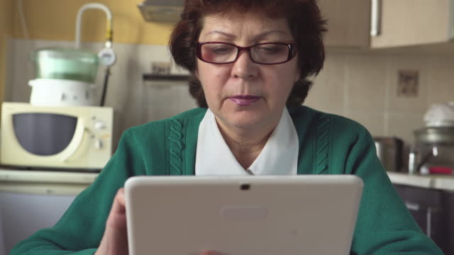 Portrait of a mature woman with a glasses uses a Tablet PC at home video
