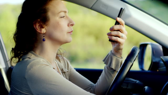 Portrait of a middle-aged woman in depression. Sits inside the car with the phone in his hand, suffers. Concept - depression, women's problems video