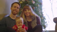Portrait of a mother, father, and their baby in front of the Christmas tree video