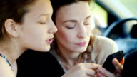Portrait of a mother with her daughter 11 years. Cute communicate, together use a mobile phone. Happy together video