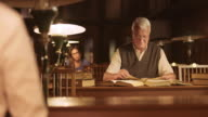 DS Portrait of senior man reading in library at night video