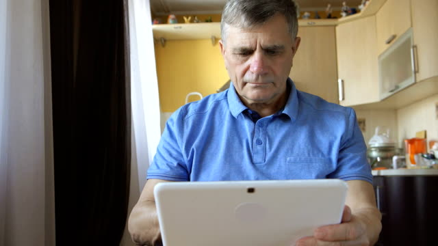 Portrait of a senior man types a tablet PC at home video