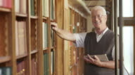 DS Portrait of senior man with tablet in library video