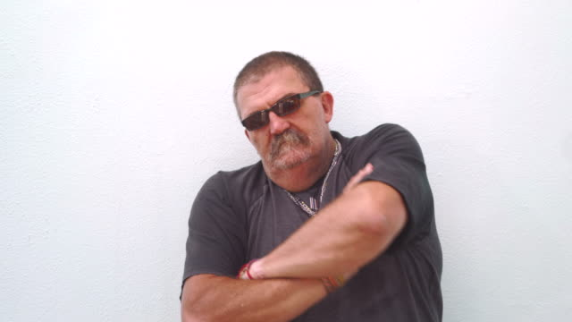 Portrait of a senior man with crossed arms and sunglasses video