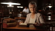 DS Portrait of senior woman reading in library at night video