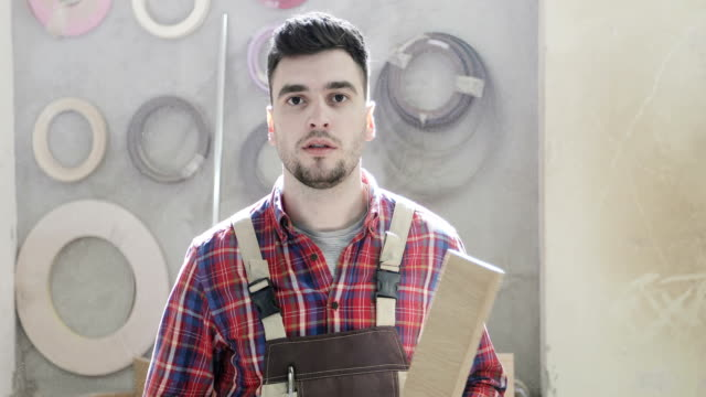 4K Portrait of a serious carpenter in a construction overall in a furniture factory. video