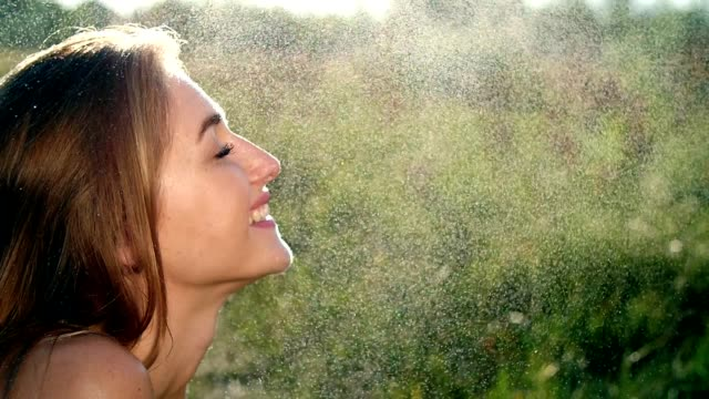 Portrait of a sexy, beautiful young blonde girl, under a light summer rain, in the sun rays, on a green meadow. The girl smiles, Her skin shines, radiates health. Image of happiness video