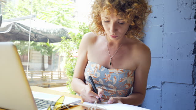 Portrait of a successful woman freelancer working at cafe. video