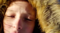 Portrait of a teenage boy close up. The boy corrected hood. Sunny winter evening in the forest. Strong wind. video