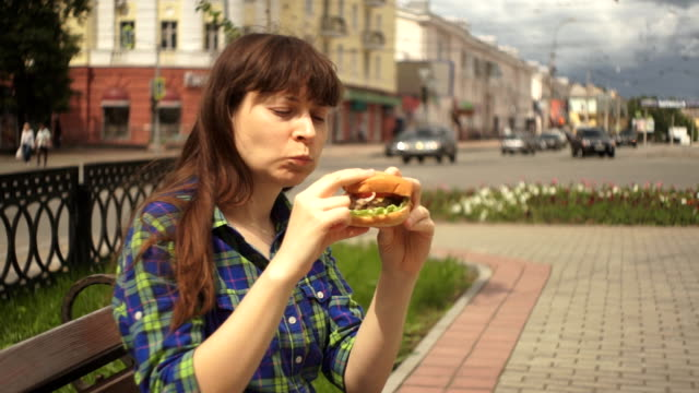 Portrait of a woman biting a burger in the street next to a busy road video