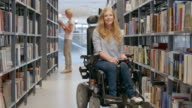 LD Portrait of woman in wheelchair smiling in library aisle video