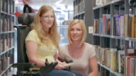 LD Portrait of woman in wheelchair with friend in library video
