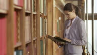 LD Portrait of woman reading a book by library shelf video