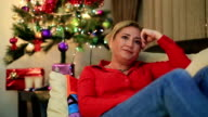 Portrait of a  woman sitting near the christmas tree video
