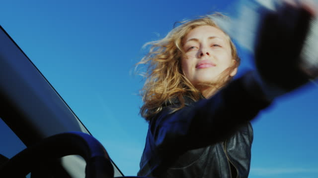 Portrait of a young attractive woman who rubs the windshield of her car video