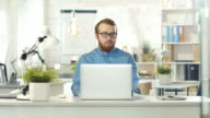 Portrait of a Young Bearded Man with Glasses Sitting at His Desk Using Notebook. He Sits in a Light and Modern Office. video