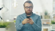 Portrait of a Young Bearded Man with Glasses Sitting at His Desk in a Bright Office Using Smartphone. video