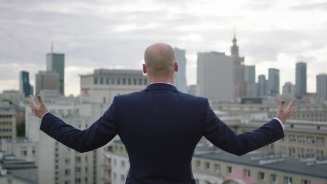 Portrait of a young businessman. Opening arms. Cityscape in the background video