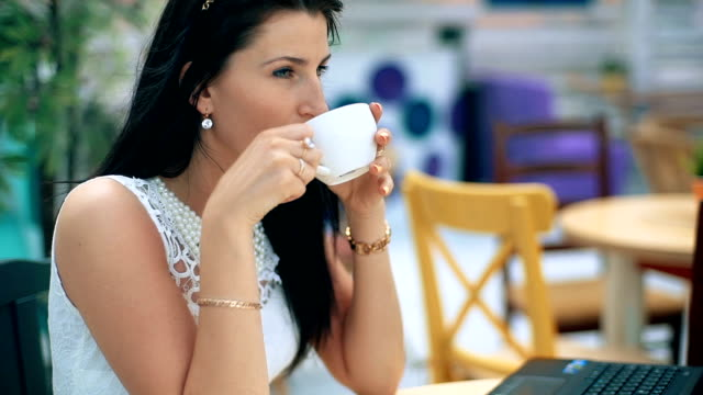 Portrait of a young businesswomen enjoying coffee during work on notebook video
