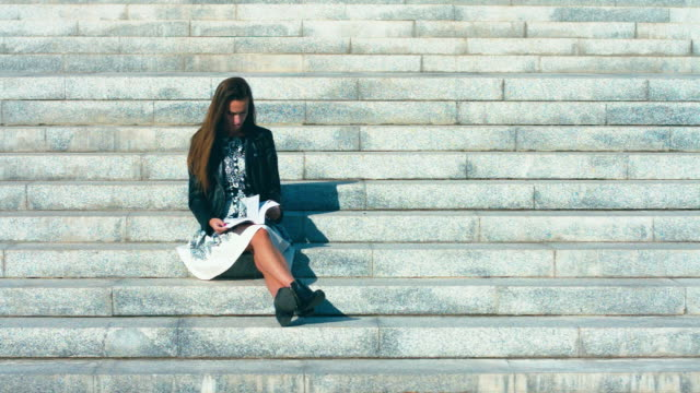 Portrait of a young caucasian teen girl with a book sitting on college stairs video