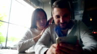 Portrait of a young couple with smartphone sitting in a restaurant video